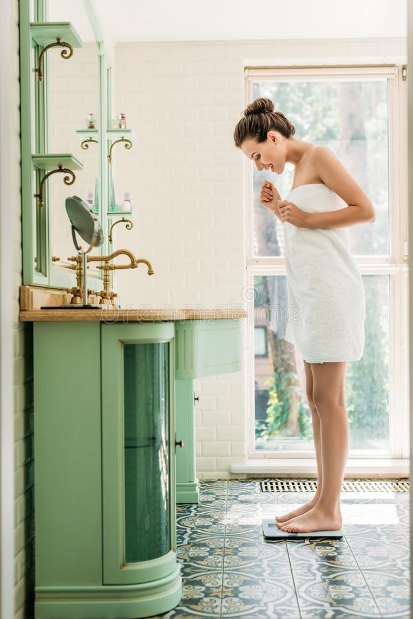 happy young woman in towel standing on digital scales royalty free stock photography