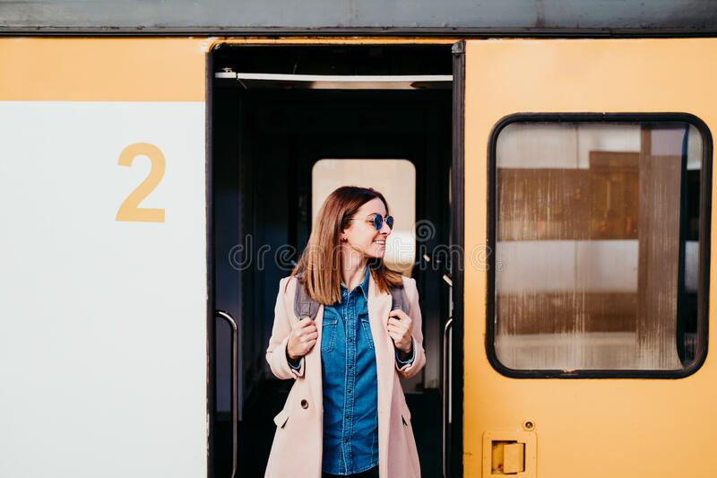 happy young woman at train station. Travel concept royalty free stock images