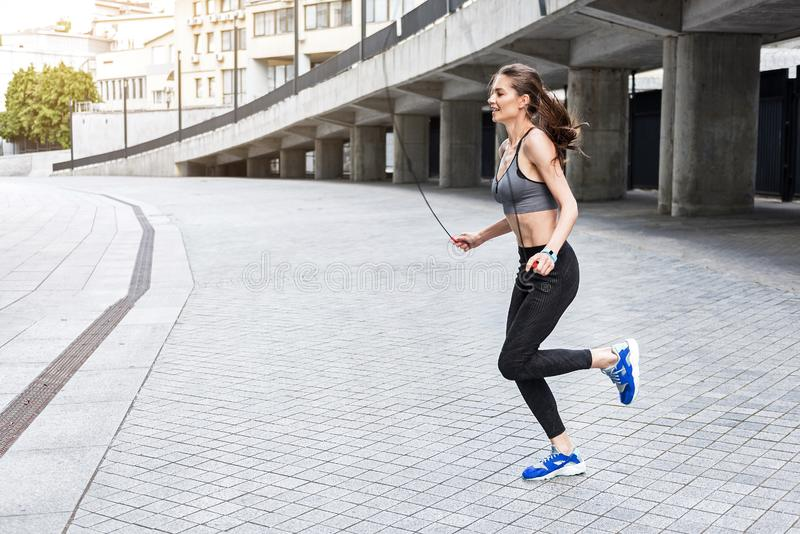 Happy young woman training with jumping-rope royalty free stock image