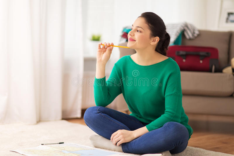 Happy young woman with travel map at home stock photography
