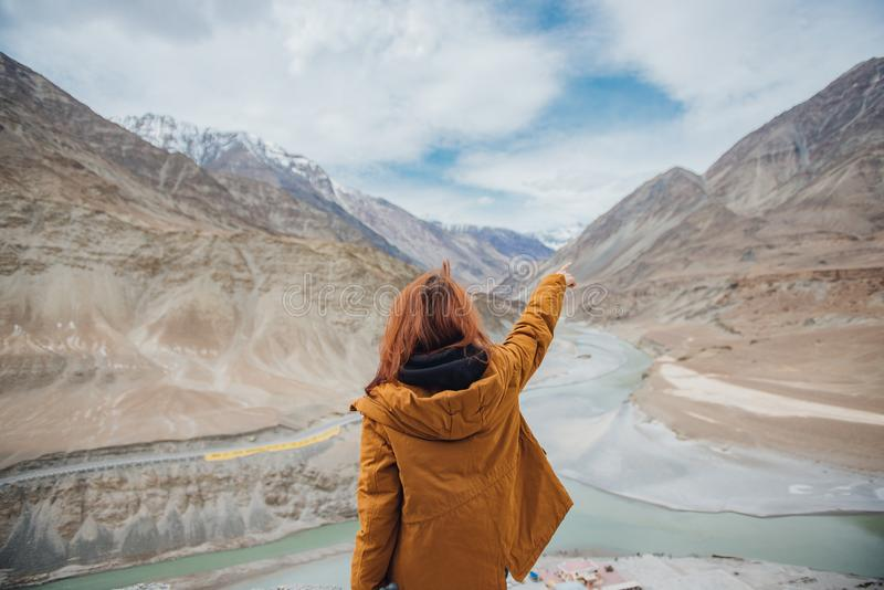 Happy young woman traveler enjoy the beautiful view at confluence of zanskar and indus rivers in leh. stock image