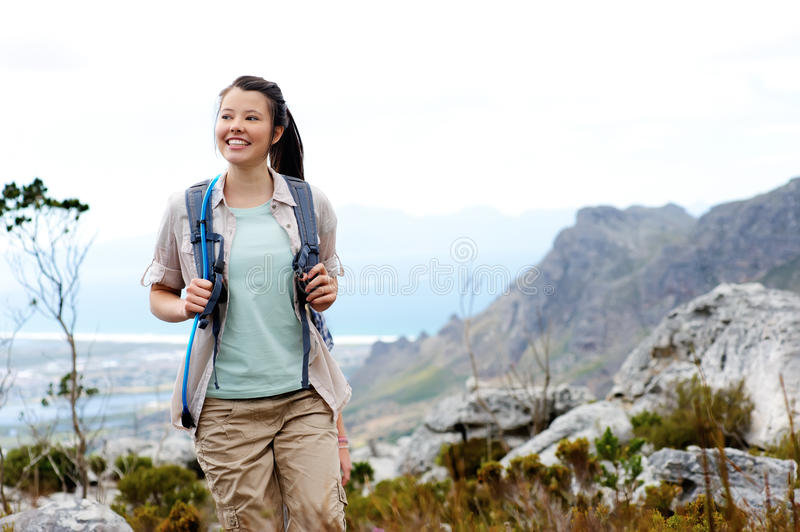 Happy young woman trekking in nature royalty free stock image