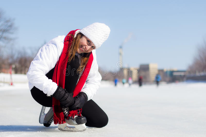 Happy young woman tying her ice skates in winter royalty free stock photography