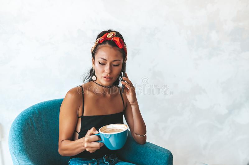 Happy young woman using mobile phone in cafe stock photography