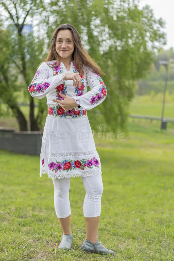 Happy young woman in the Ukrainian national clothes in the park. Woman in embroidery. Vertical photo royalty free stock photography