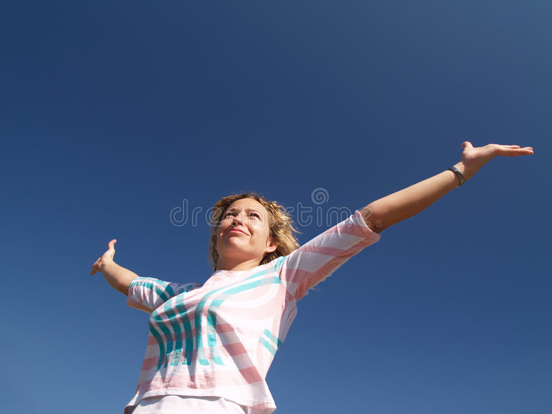 Happy young woman under blue sky royalty free stock photo