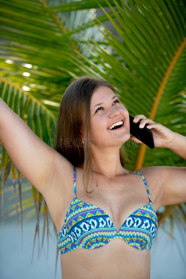 Happy young woman under palm tree talking on the smart phone stock photos