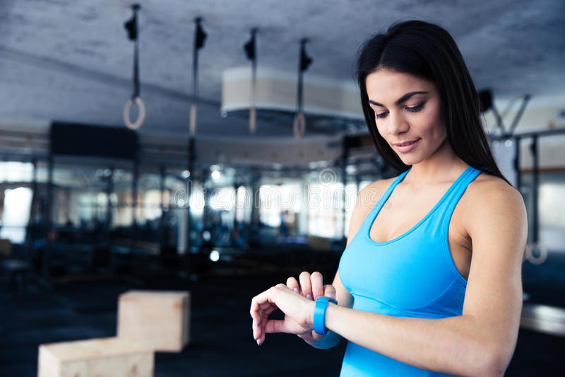 Happy young woman using activity tracker stock image