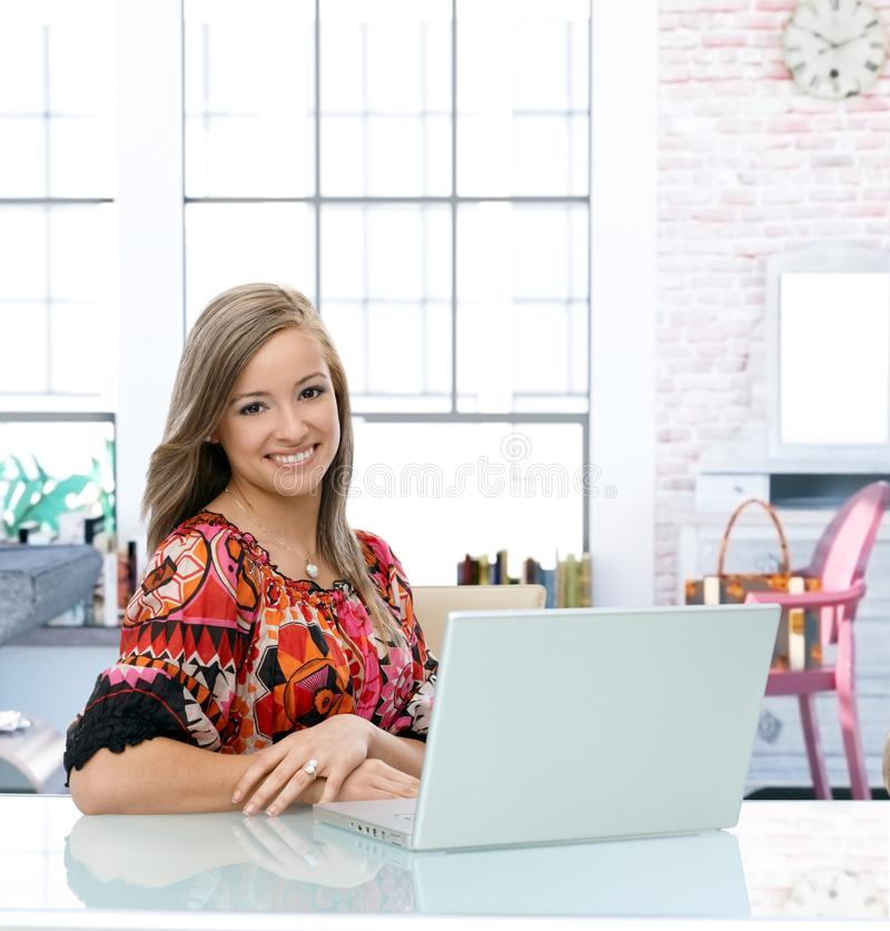 Happy young woman using laptop at home stock photos