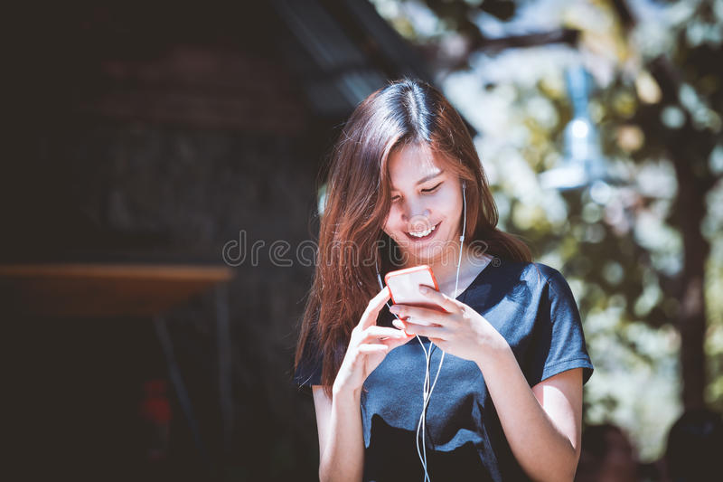 Happy young woman using and listening music on smartphone royalty free stock photography