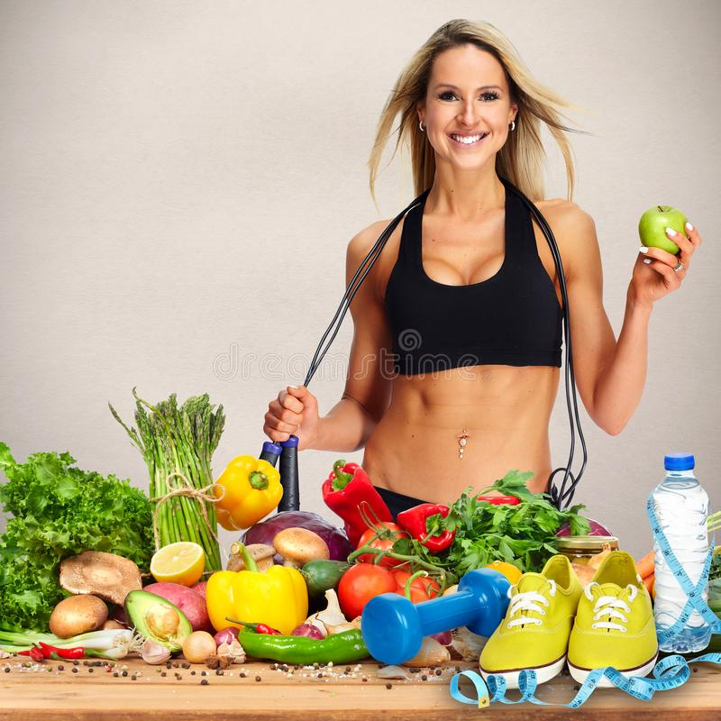 Happy fitness woman. Happy young woman and vegetables on the table stock images