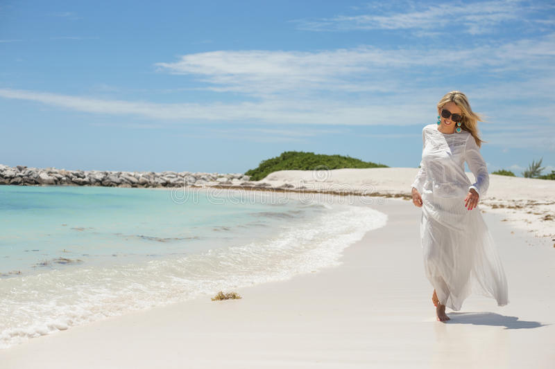 Happy young woman walking on the beach stock images