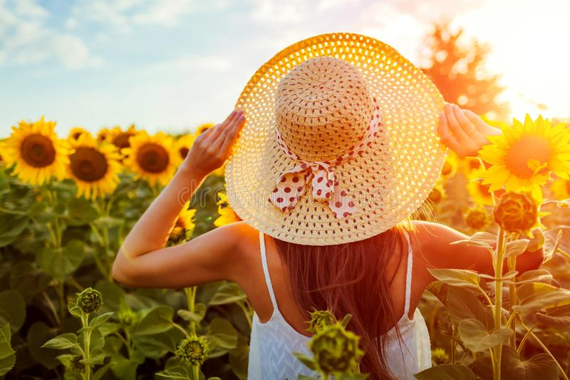 Young woman walking in blooming sunflower field holding straw hat. Summer vacation royalty free stock photo