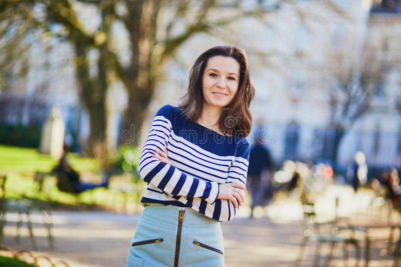 Happy young woman walking in the Luxembourg garden of Paris royalty free stock photo