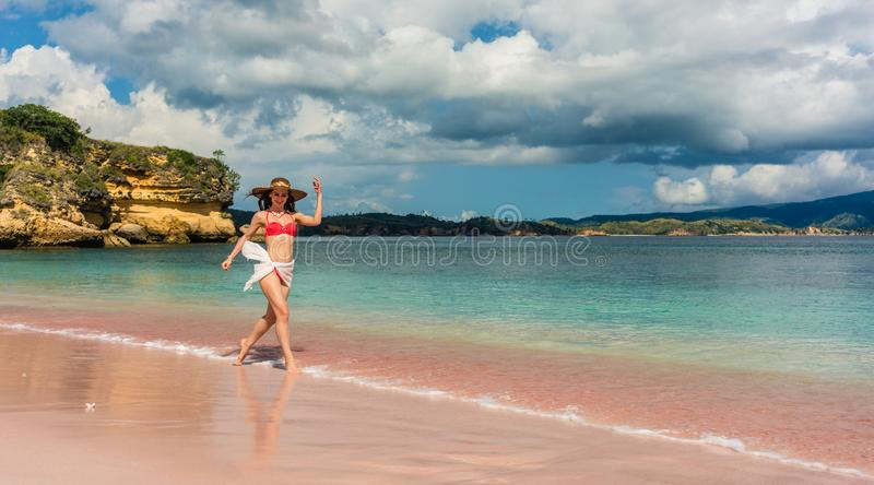 Happy young woman walking through shallow sea water on the beach stock photo