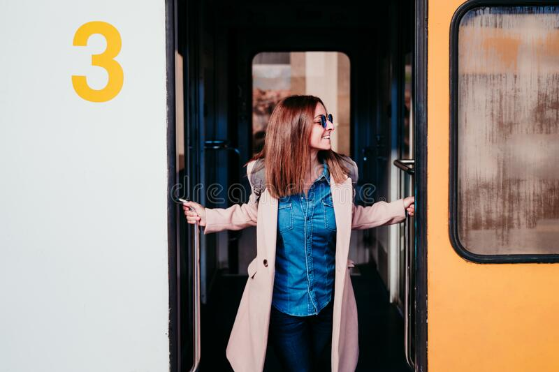 happy young woman walking at train station. Travel concept royalty free stock photo