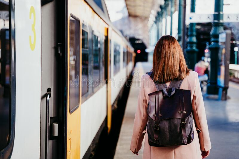 happy young woman walking at train station. Travel concept royalty free stock images