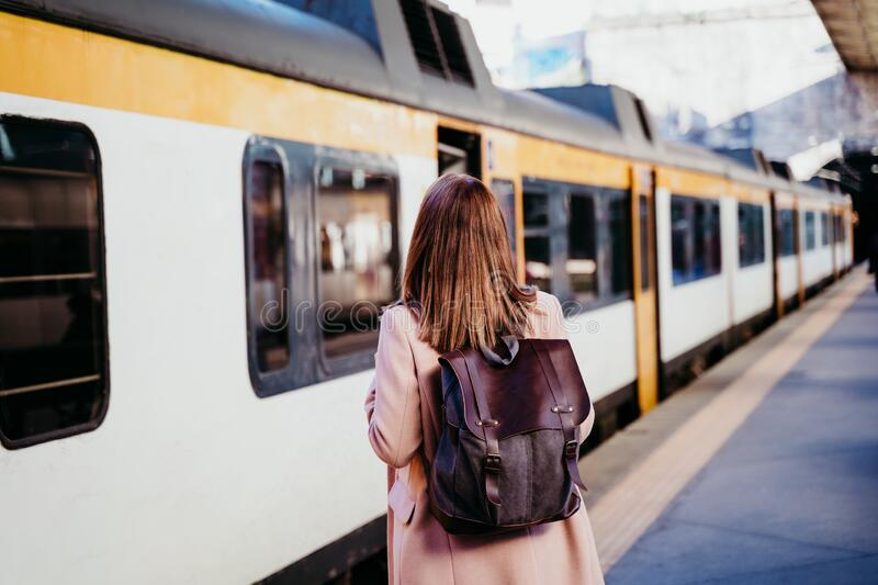 happy young woman walking at train station. Travel concept stock photo