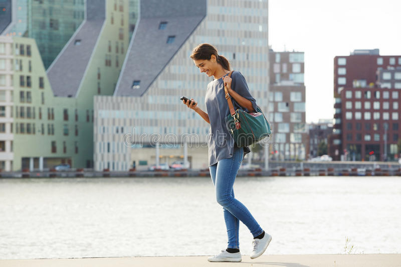 Happy young woman walking water in city with mobile phone. Full length portrait of happy young woman walking water in city with mobile phone royalty free stock photo
