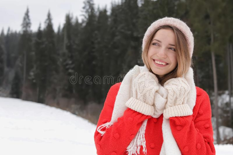Happy young woman in warm clothes, space for text. Winter vacation. Happy young woman in warm clothes outdoors, space for text. Winter vacation stock photography