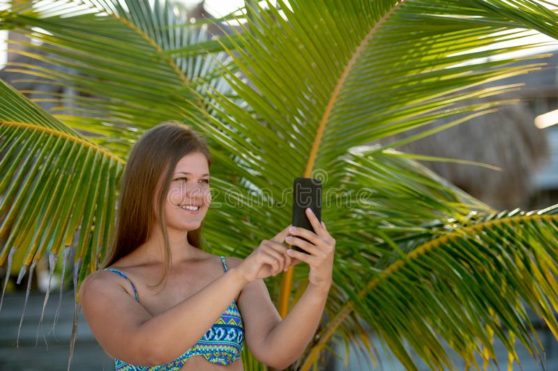 Happy young woman makes selfie on the beach. Happy young woman wearing bikini taking selfie using smartphone in the summer day between palm on the beach in royalty free stock photos