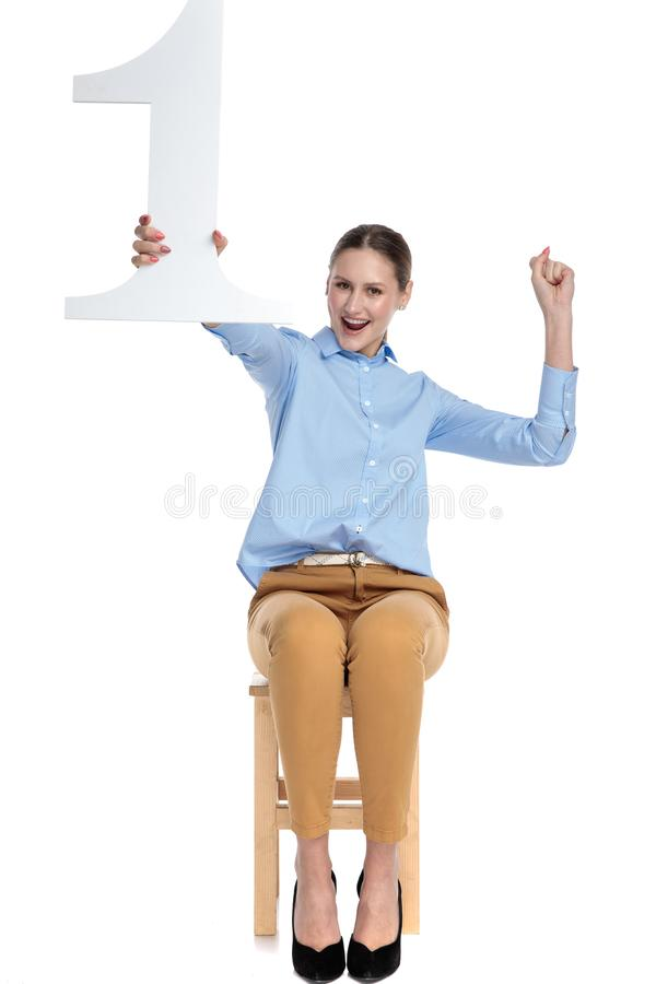 Happy young woman holding 1st sign and celebrating victory royalty free stock photography