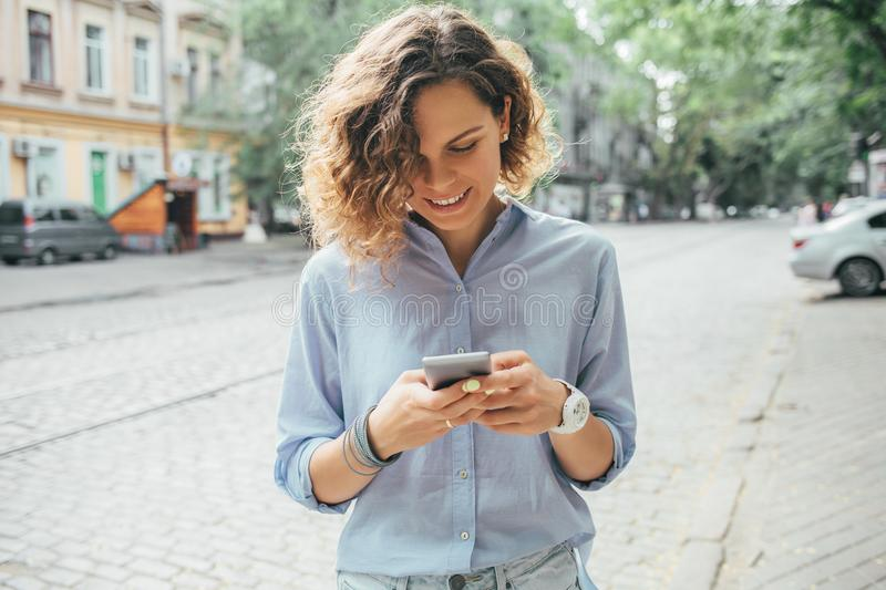 Happy young woman wearing blue shirt using mobile phone royalty free stock photos