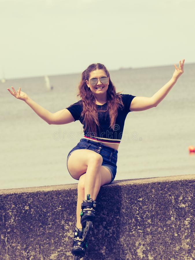 Happy young woman wearing roller skates stock photos