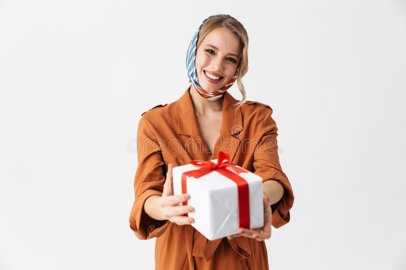 Happy young woman wearing silk stylish scarf posing isolated over white wall background holding gift box royalty free stock photography