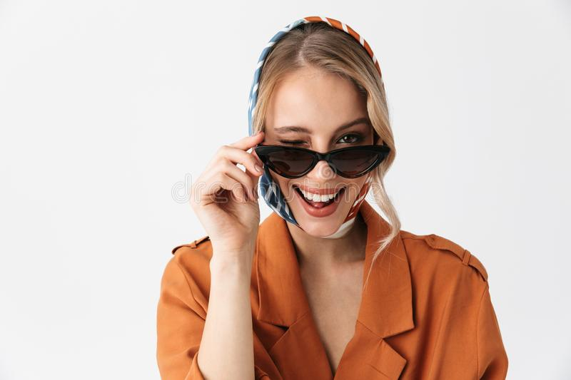Happy young woman wearing silk stylish scarf posing isolated over white wall background wearing sunglasses winking royalty free stock images