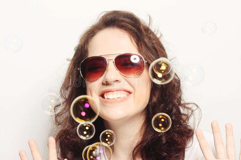 Young woman with soap bubbles. Happy young woman wearing sunglasses with soap bubbles stock photography