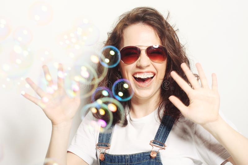 Young woman with soap bubbles. Happy young woman wearing sunglasses with soap bubbles stock photos