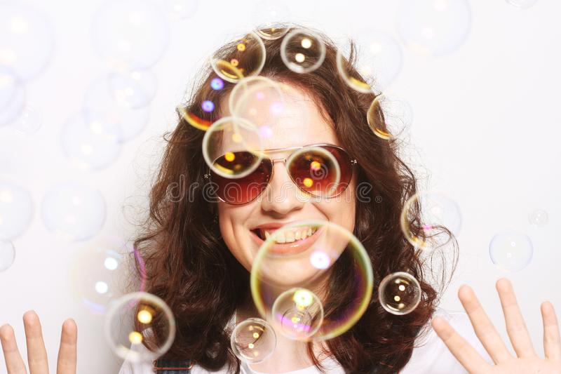 Young woman with soap bubbles. Happy young woman wearing sunglasses with soap bubbles royalty free stock photos