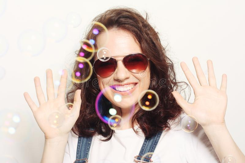 Young woman with soap bubbles. Happy young woman wearing sunglasses with soap bubbles stock image