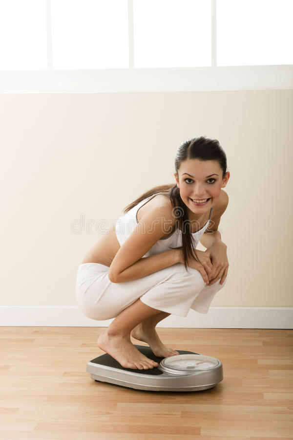 Happy young woman on weight scale stock images