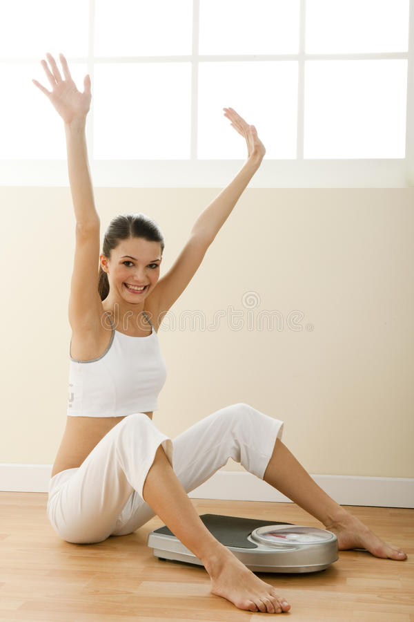 Happy young woman with weight scale stock photography