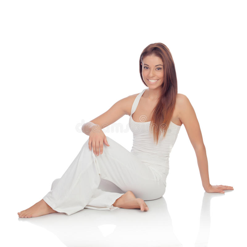 Happy young woman with white comfortable clothing sitting on the stock photos