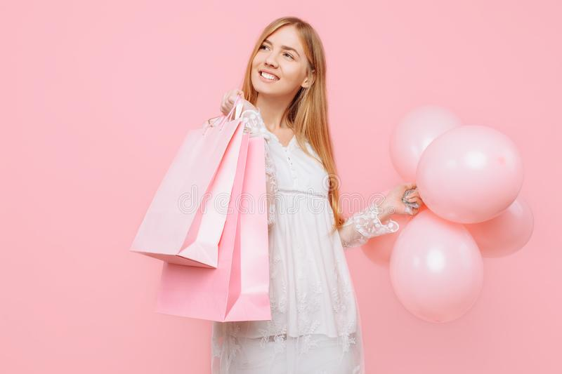 Happy young woman, in a white dress, with bags in hands and balloons, on a pink background. shopping concept. Happy young woman, in a white dress, with bags in stock photos