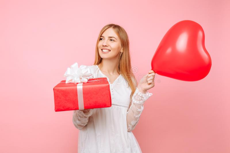 Happy young woman, in a white dress, with a gift box and balloons in their hands, on a pink background. Valentine`s Day royalty free stock images