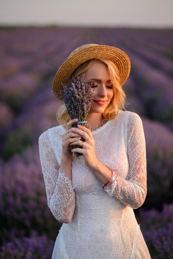 Happy young woman in white dress standing in flowering lavender field, close-up royalty free stock photography