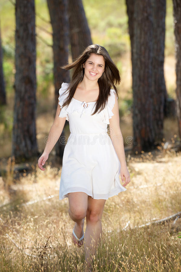Happy young woman in white dress walking in nature stock photography