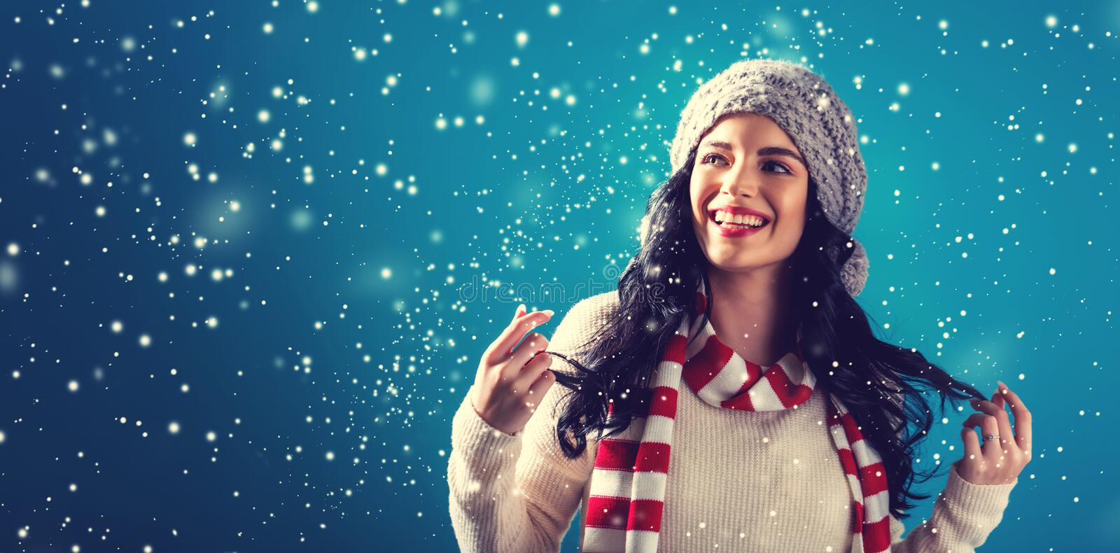 Happy young woman in winter clothes. In a snowy night stock photos