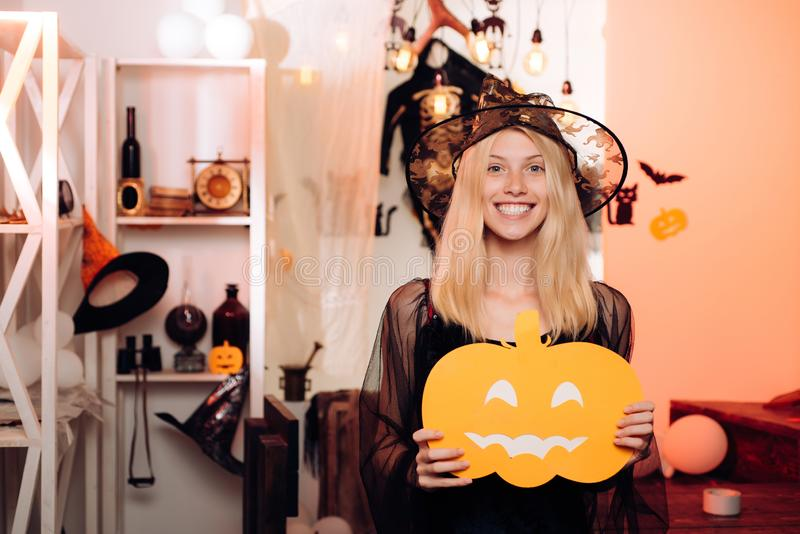 Happy young women in witch halloween costumes on party over isolated background. Portrait of a gorgeous blonde witch in. Happy young woman in witch halloween royalty free stock photo