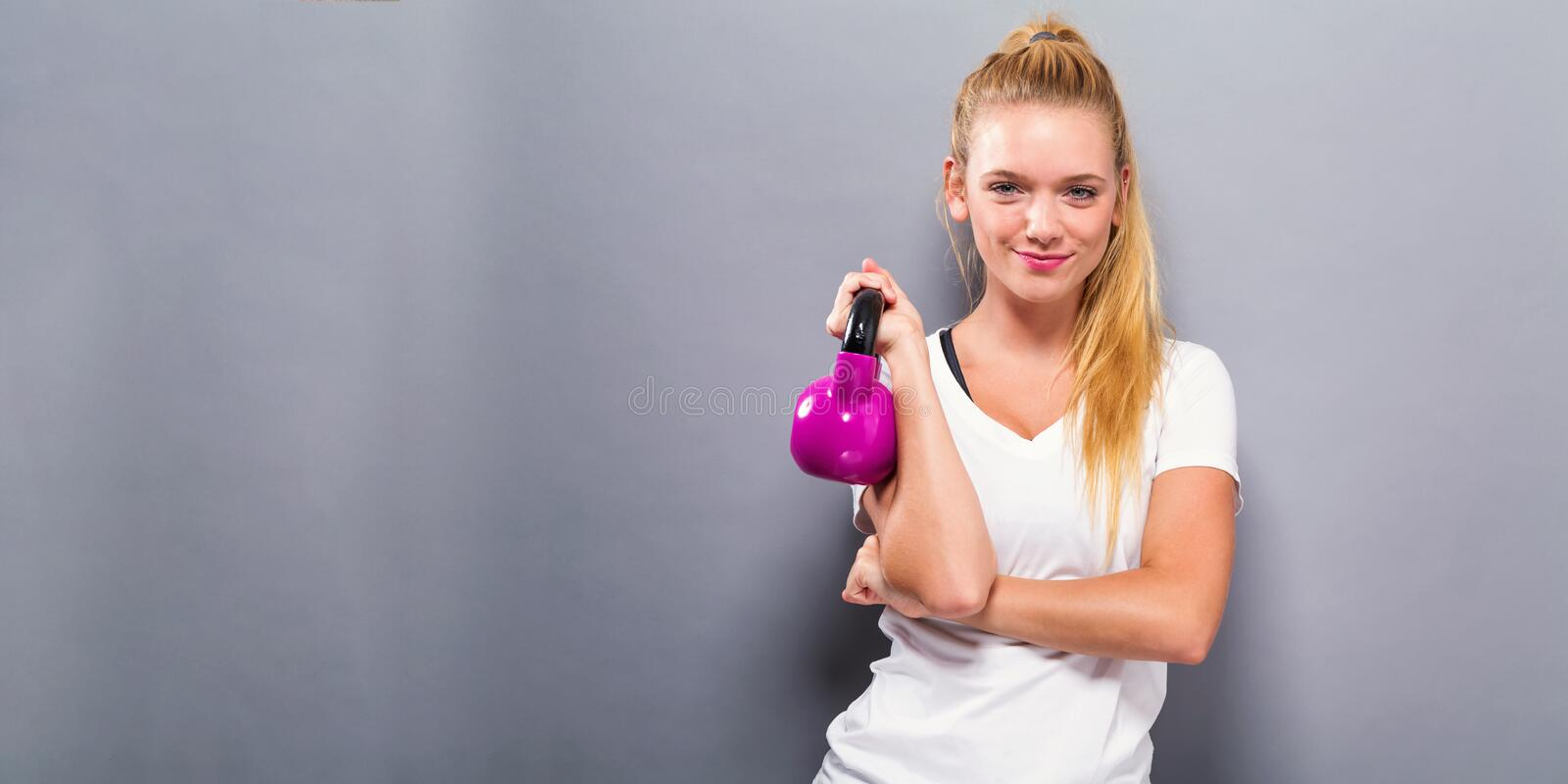 Happy young woman with a kettlebell royalty free stock photos