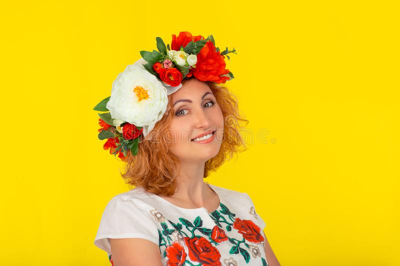 Happy young woman in a wreath of flowers stock images