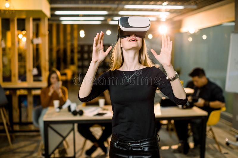 Happy young woman adjusting her virtual reality headset and excited playing video game in VR device while standing at. Happy young women adjusting her virtual stock image