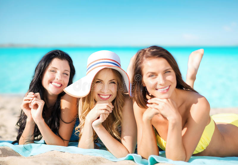 Happy young women in bikinis on summer beach. Summer holidays, travel, people and vacation concept - happy young women in bikinis sunbathing over exotic tropical stock photography