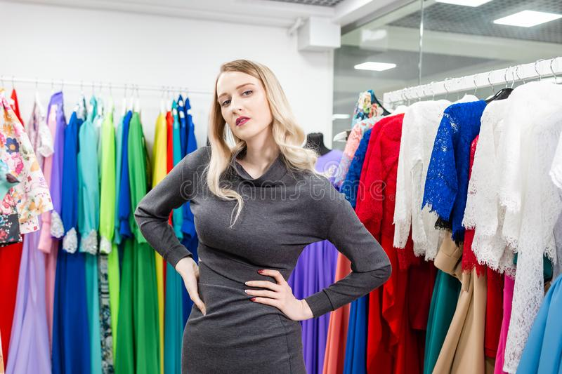 Portrait of a girl on the background of clothes on hangers in the clothing store. Happy young woman choosing clothes royalty free stock photo
