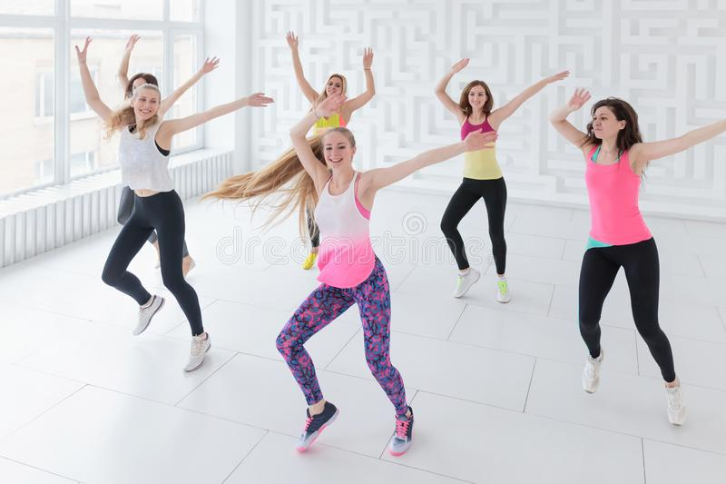 Happy young women with coach having a fitness dance class. With hands raised up stock images