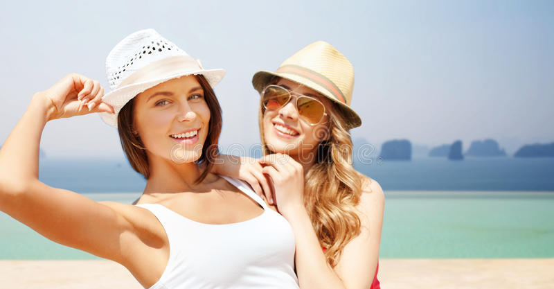 Happy young women in hats on summer beach. Summer holidays, travel, people and vacation concept - happy young women in hats over infinity edge pool background stock photos